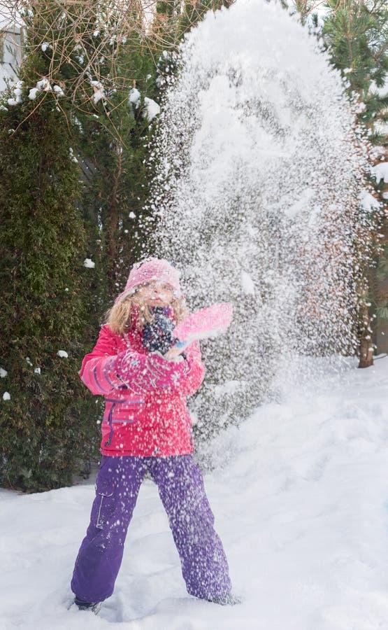 Små Caucasian blonda flickor i rött omslag spelar med snö på gran-träd suddighetsbakgrund royaltyfri foto