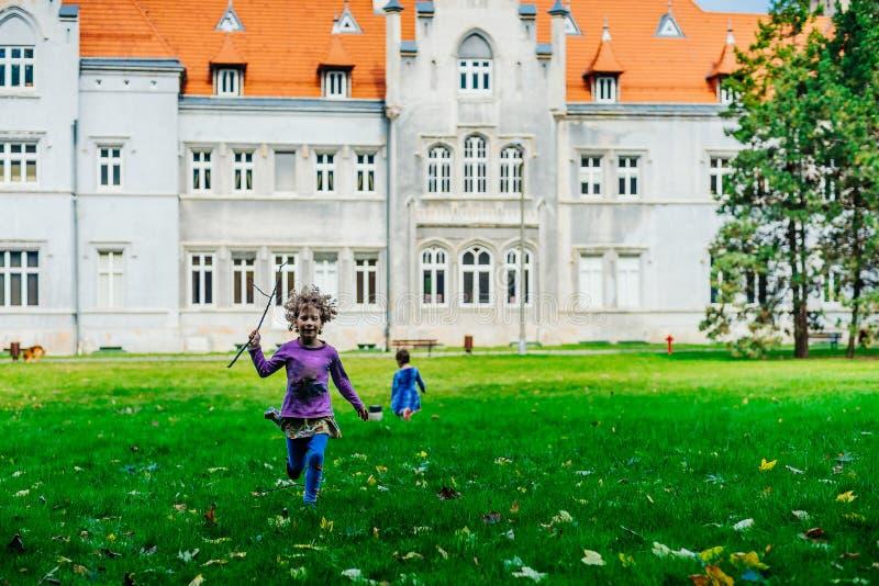 Små caucasian flickor som kör runt om hösten, parkerar royaltyfri bild