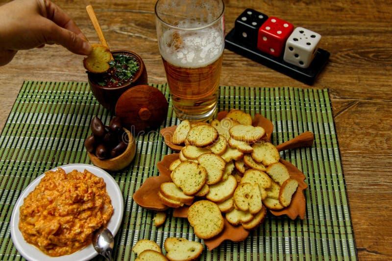 Små chiper för melbarostat bröd eller bruschettapå trätabellen med öl och såser arkivfoto