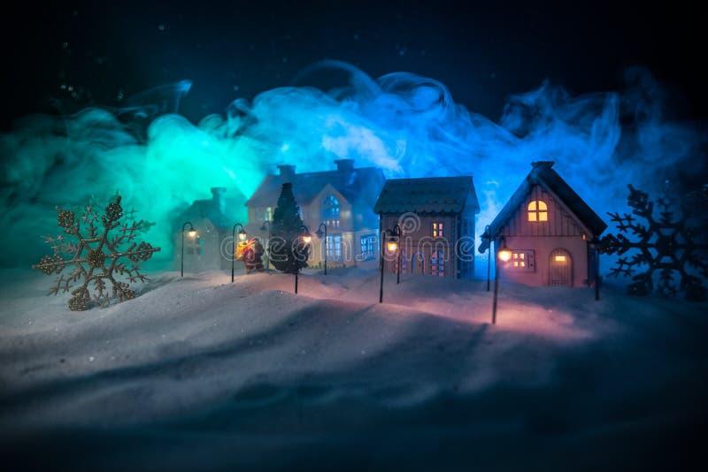 Små dekorativa gulliga små hus i snö på natten i vinter, miniatyrhuset för jul och för nytt år i snön på natten med arkivfoton
