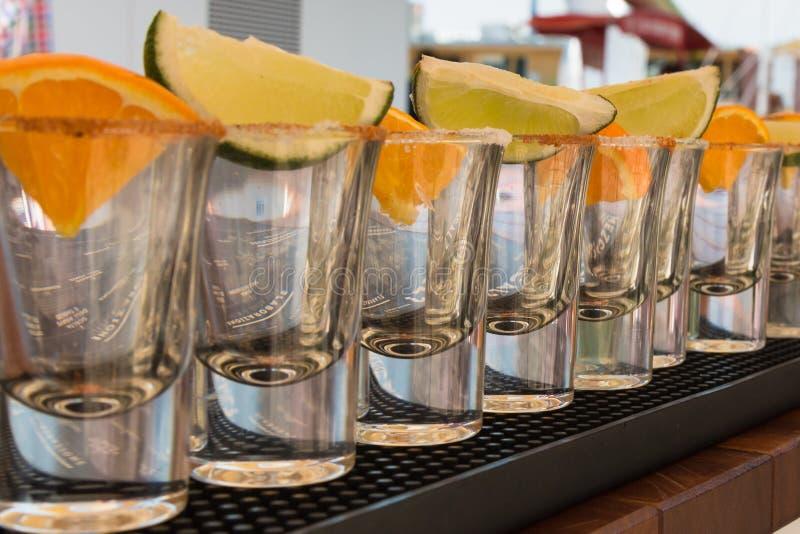 Små exponeringsglas i överensstämmelse med apelsin- och limefruktskivor som är klara till Tequ arkivbild