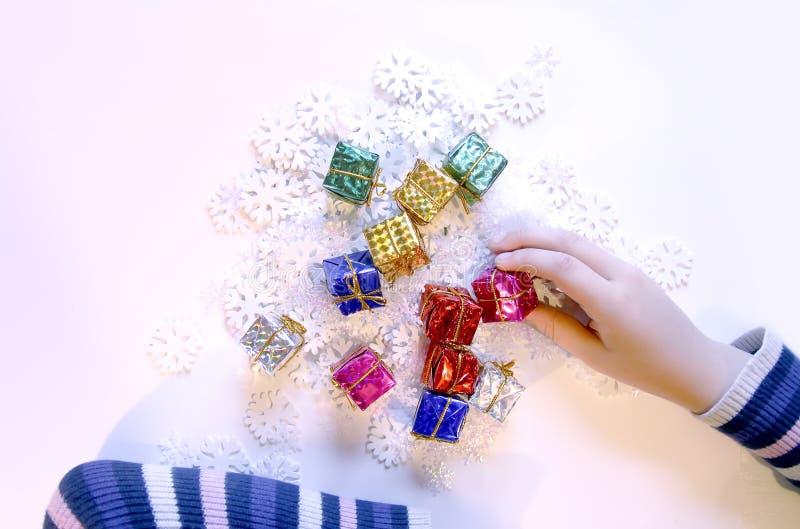 Små färgrika gåvaaskar i child& x27; s-händer Jul- och NewYear garneringprocess royaltyfria bilder