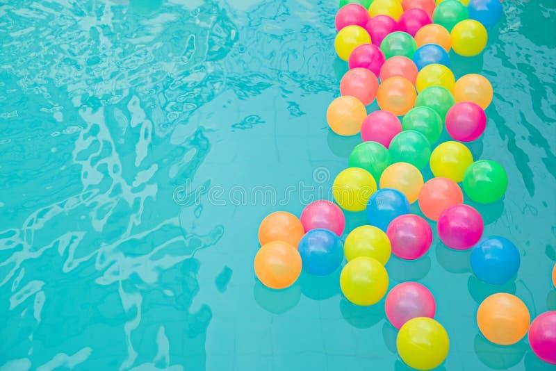 Små färgrika strandbollar som svävar i simbassäng, gör sammandrag begreppet för pölparti s royaltyfria foton