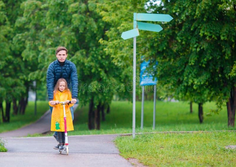 Små förtjusande flickor som rider på sparkcyklar med farsan i höst, parkerar utomhus arkivfoton