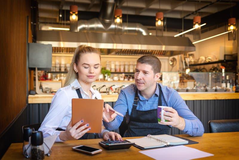 Små familjrestaurangägare som diskuterar finans som beräknar räkningar och kostnader av deras små och medelstora företag royaltyfria bilder