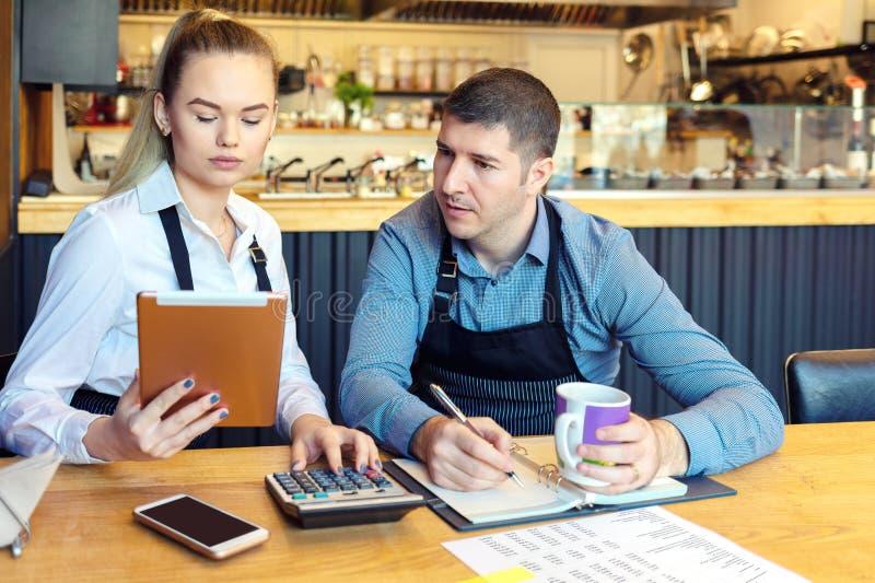 Små familjrestaurangägare som diskuterar finans som beräknar räkningar och kostnader av deras nya små och medelstora företag arkivfoto