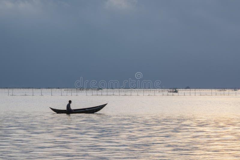 Små fiskebåtar och ensam man i fjärden med magi av himlen och molnen på soluppgångdel 6 royaltyfri foto