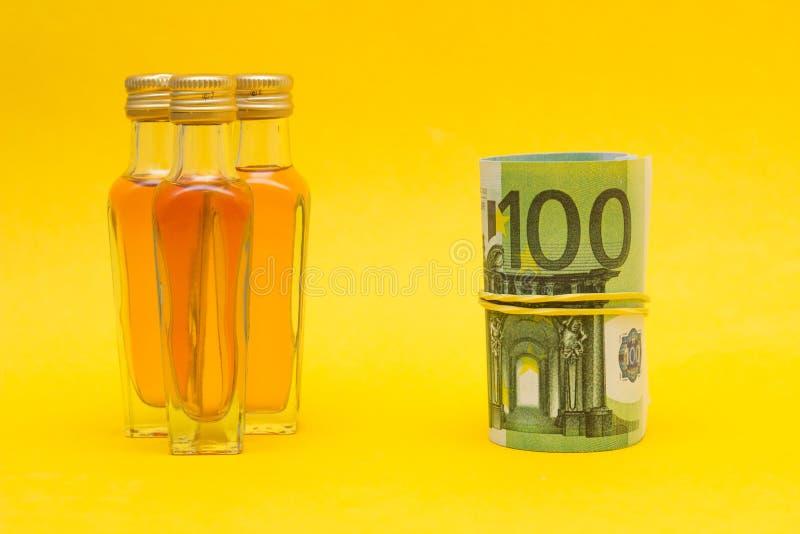 Små flaskor med alkohol och europengar, inkomst från alkoholhandeln, prishöjning, närbild royaltyfria bilder