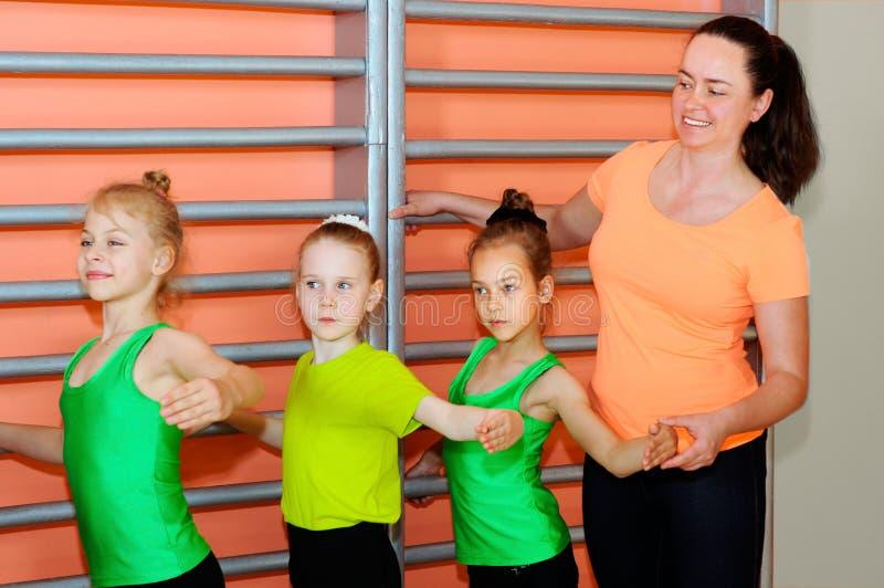 Små flickor för gymnastiklagledareundervisning arkivfoto