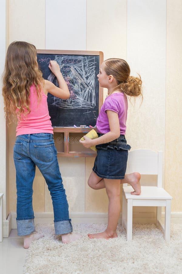Små flickor i lekrummet målar på svart tavla arkivbild