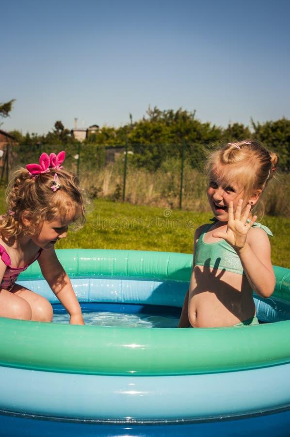 Små flickor i simbassäng royaltyfri bild