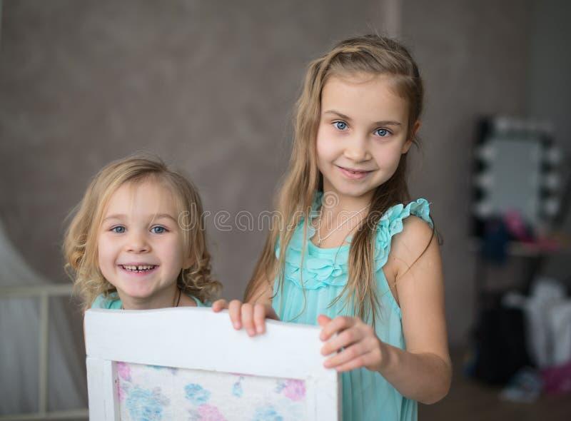 2 små flickor i vitt sitta för klänningar royaltyfri bild