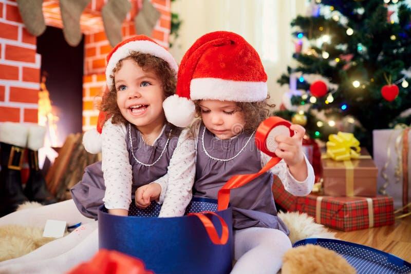 Små flickor kopplar samman på jul som sitter på golvet i jultomtenmummel arkivbilder