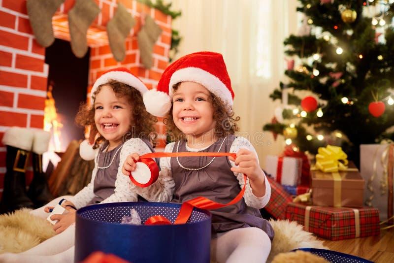 Små flickor kopplar samman på jul som sitter på golvet i jultomtenmummel royaltyfri foto