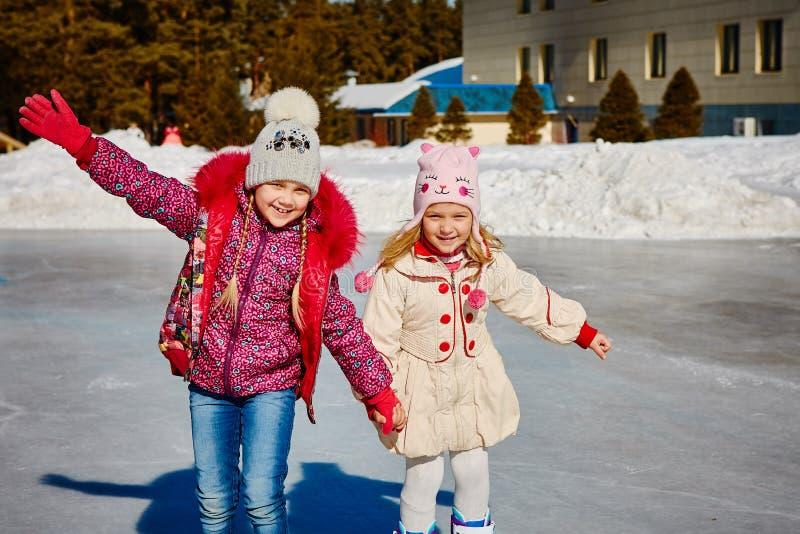 Små flickor lär att åka skridskor De är skratta och lyckliga Begrepp av kamratskap och roliga ferier arkivbild