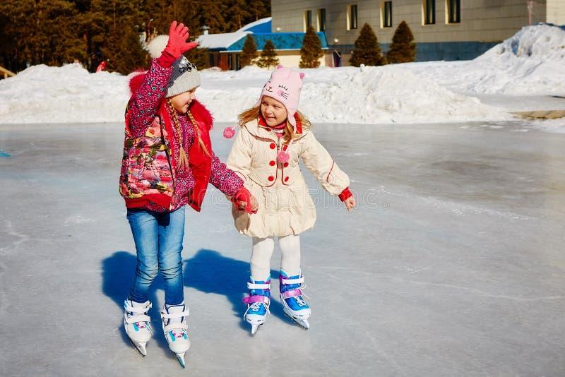 Små flickor lär att åka skridskor De är skratta och lyckliga Begrepp av kamratskap och roliga ferier royaltyfri foto