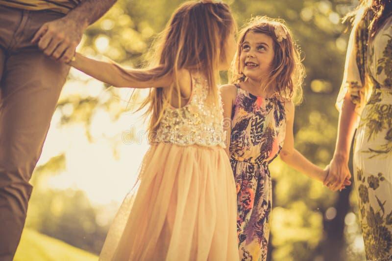 Små flickor med föräldrar i natur royaltyfri bild