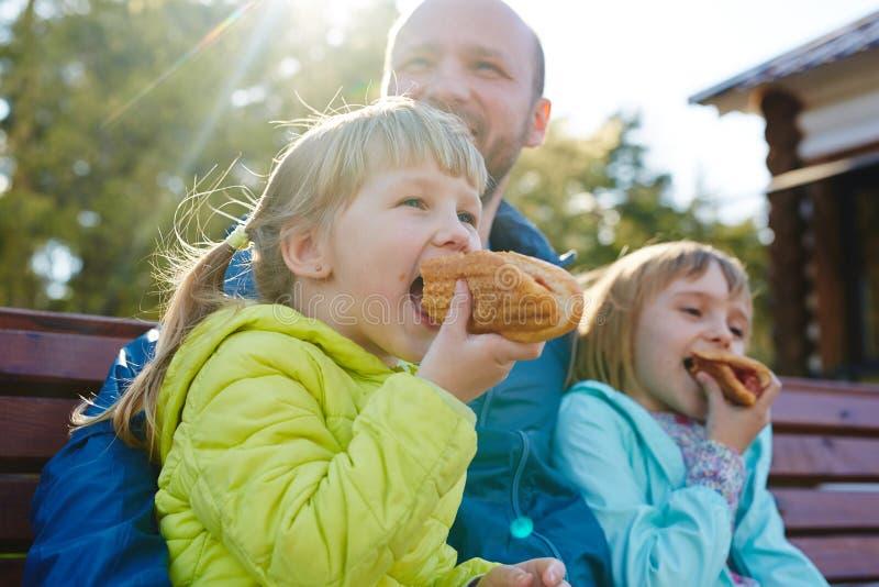 Små flickor med läckra hotdogs royaltyfri foto
