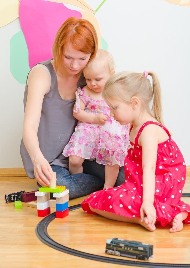 Små flickor och moder som spelar med järnvägen royaltyfri foto