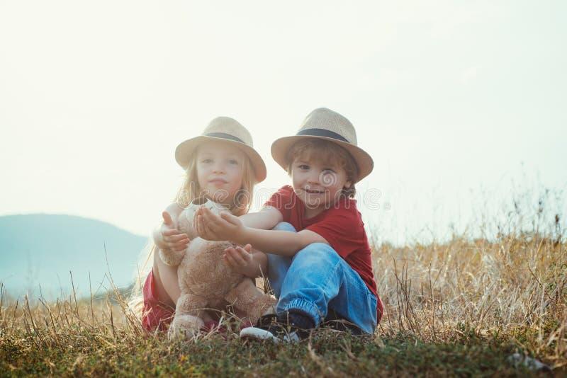 Små flickor och små pojkar njuter av liv och natur Barn har sommarglädje Barnomsorg Glad dag Det är bara kul. arkivfoton