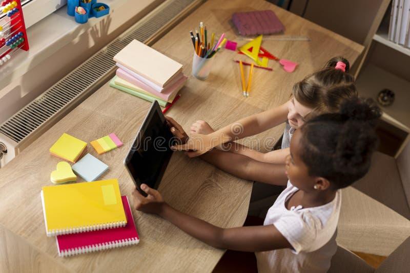 Små flickor som använder minnestavladatoren arkivbilder