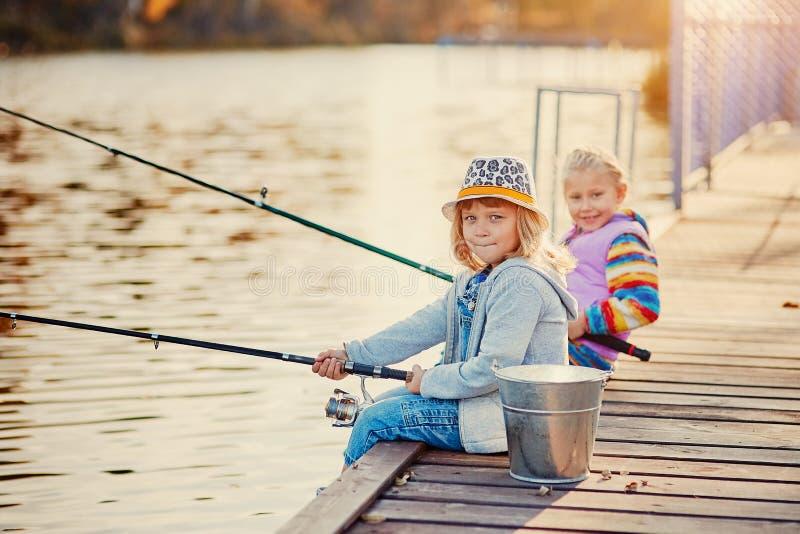 Små flickor som fiskar på sjön som sitter på en träponton arkivfoton