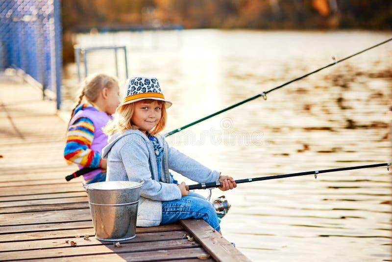 Små flickor som fiskar på sjön som sitter på en träponton royaltyfri foto