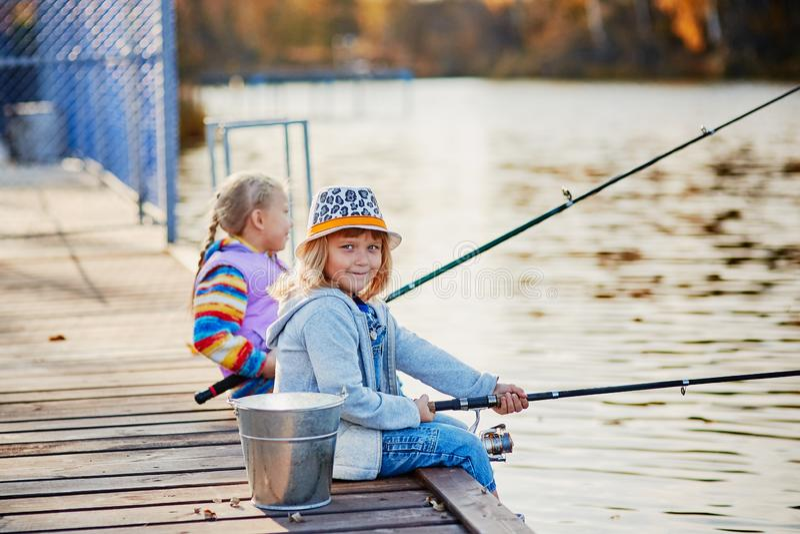 Små flickor som fiskar på sjön som sitter på en träponton royaltyfri fotografi