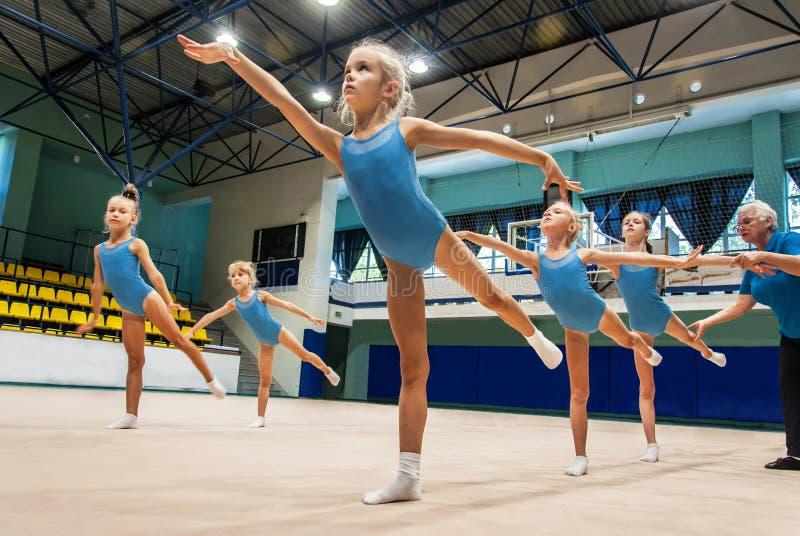 Små flickor som gör övning i idrottshall royaltyfria bilder