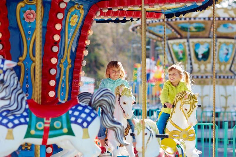 Små flickor som har gyckel på karusell royaltyfria foton
