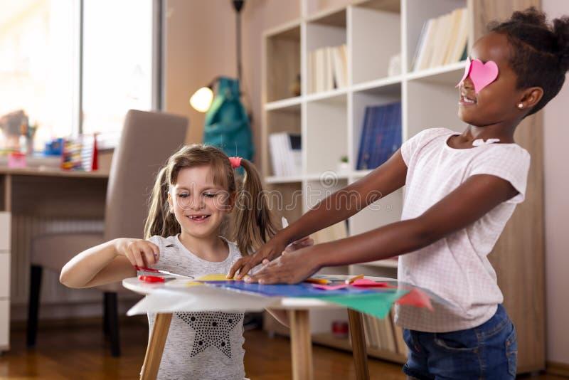 Små flickor som klipper färgrikt papper arkivbild
