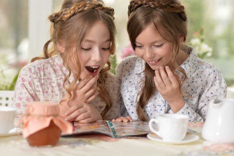 Små flickor som läser en tidskrift arkivfoton