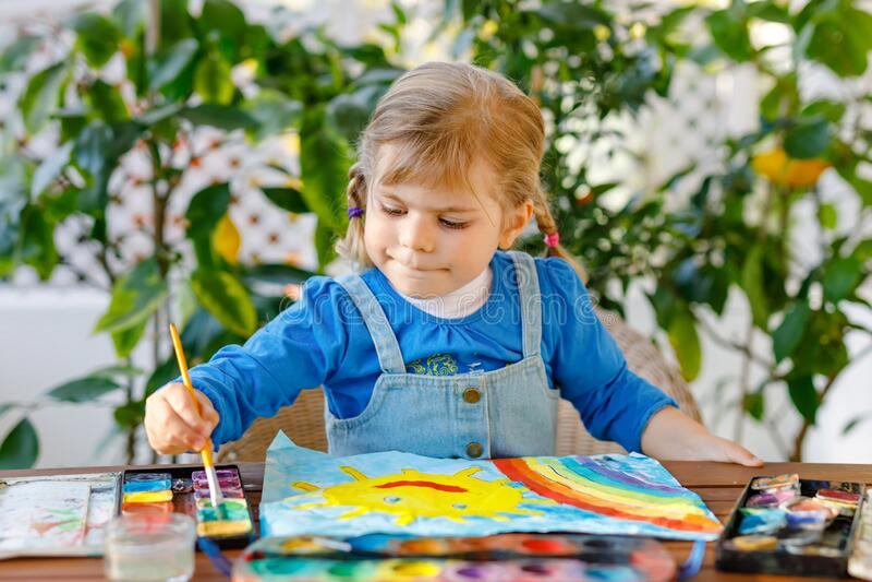 Små flickor som målar regnbåge och sol med vattenfärger under karantänsjukdom med pandemiskt coronavirus Barn royaltyfri foto