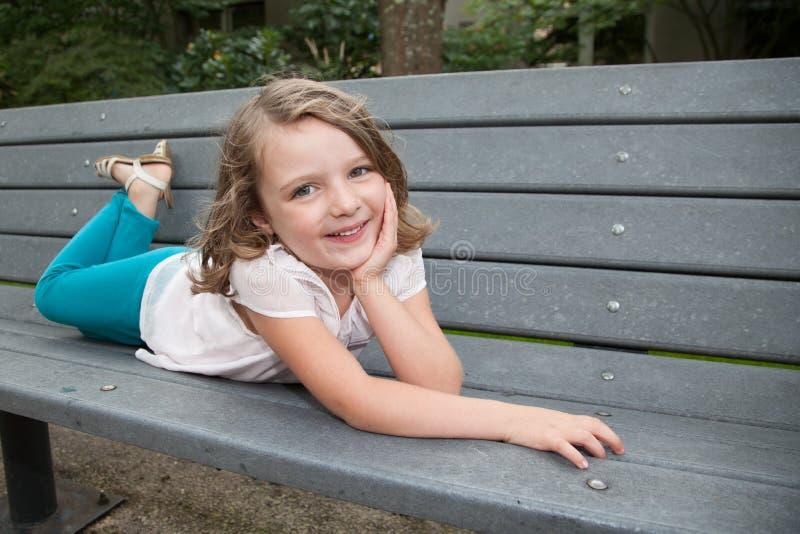 Små flickor som poserar på grå bänkdet fria, parkerar sommardag royaltyfria foton