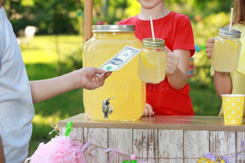 Små flickor som säljer naturlig lemonad till pojken parkerar in Uppfriskande drink f?r sommar royaltyfri bild