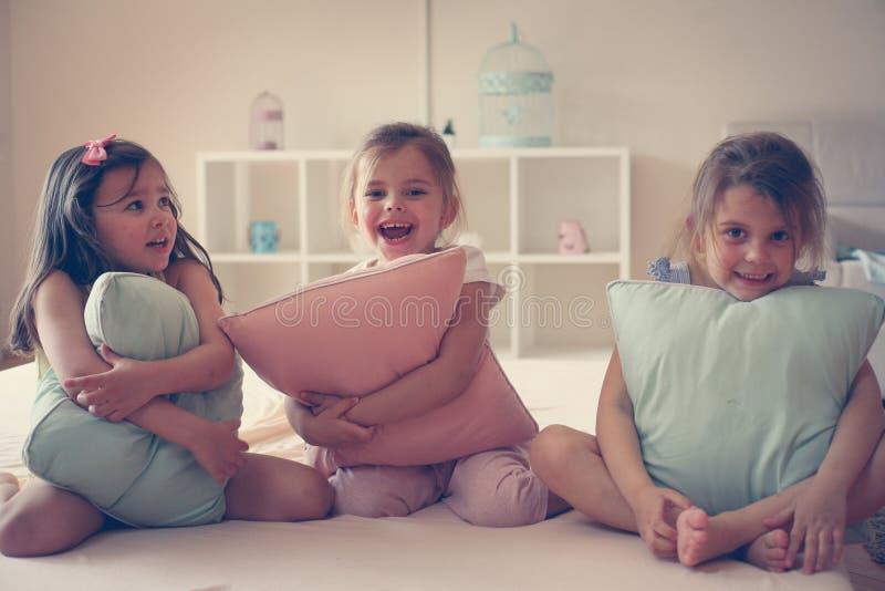 Små flickor som sitter på säng och ser kameran fotografering för bildbyråer