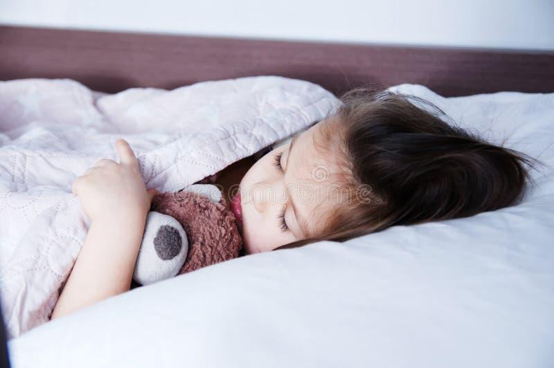 Små flickor som sover att ligga på säng sömnschema i inhemsk livsstil gulligt barn med björnen arkivbilder