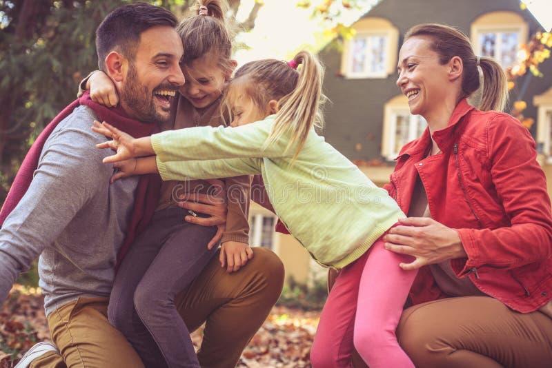 Små flickor som spelar med föräldrar som kramar fadern arkivbild