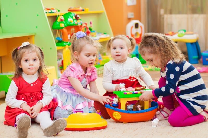 Små flickor som spelar med leksaker i lekrum arkivfoton
