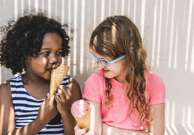 Små flickor som tycker om med glass royaltyfri foto