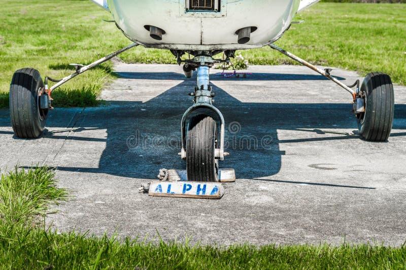 Små flygplanhjul för enkel motor och landa kugghjul på att parkera blocket med hjulkilar fotografering för bildbyråer