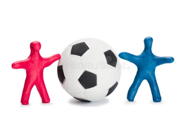 Små fotbollsspelare med kula royaltyfri bild