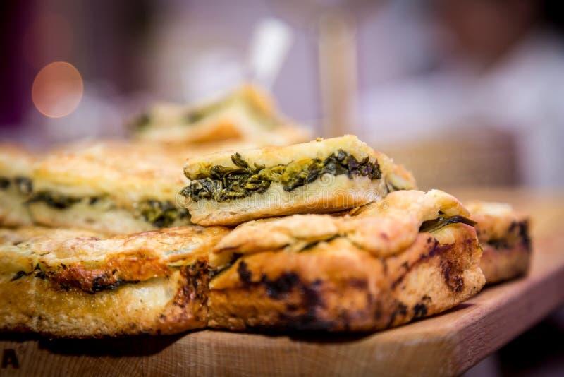 Små fyllda pizza med porkkorv och friarielli broccoli på träplattan, typisk napolitansk mat royaltyfri fotografi