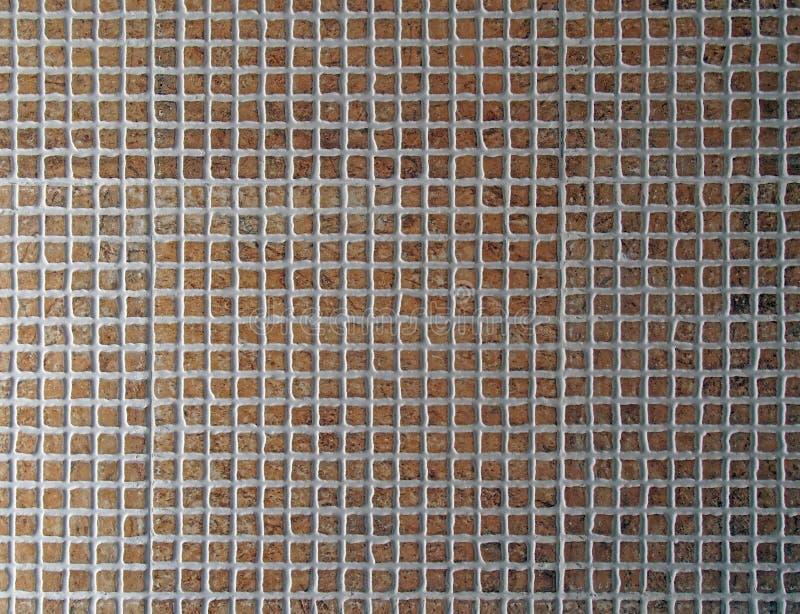 Små fyrkantiga keramiska tegelplattor i olika skuggor av brunt med vit grouting bakgrund arkivbild