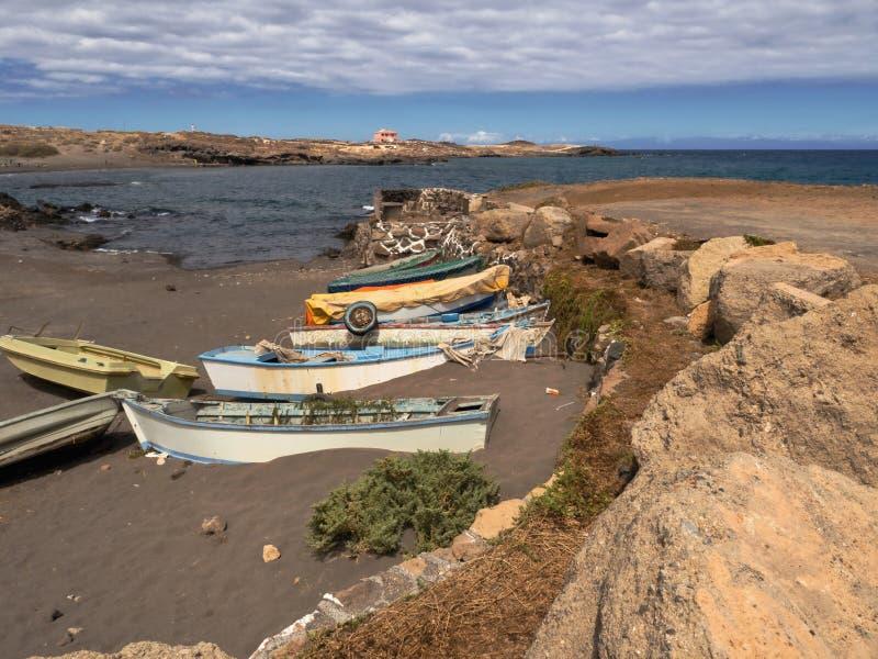Små gamla träfiskebåtar som målas colorfully, lokaliseras på den svarta Vilkansandstrand rätten framme av Atlanten royaltyfri bild