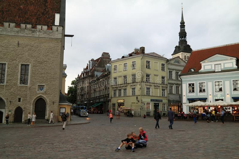 Små gladlynta turister sitter på en stenkörbana i mitten av gamla Tallinn royaltyfri fotografi