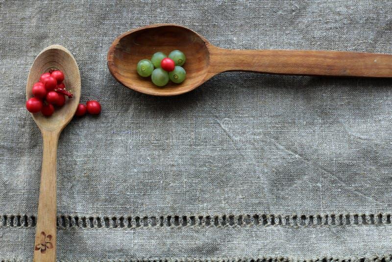 Små gröna bär av druvor och röda bär av lemongrass på två träskedar som ligger på en torkduk som göras av säckväv arkivfoto