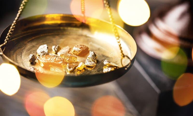 Små guld- klumpar i en antik mäta skala arkivbild