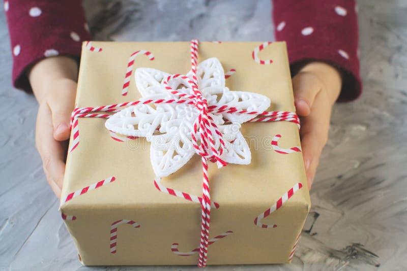 Små händer behandla som ett barn asken för gåvan för det nya året för jul för flickan den hållande, partibegrepp arkivfoton