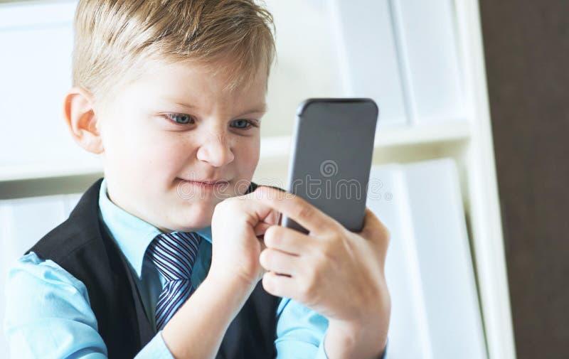 Små ilskna samtal för affärsmanframstickandepojke i regeringsställning på telefonen som sitter på skrivbordet med bärbara datorn arkivfoton